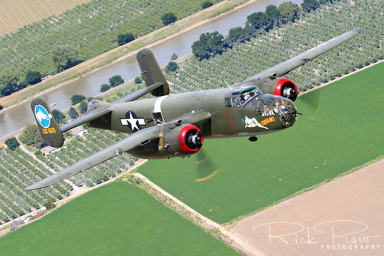 "The Collings Foundation B-25 Mitchell Medium Bomber ""Tondelayo"" flies over California's San Jauquin Valley Delta as part of the Foundation's 2006 Tour. The B-25 first gained fame when it was used in the April 1942 Doolittle Raid, in which 16 B-25B's, led by the legendary Lt Col Jimmy Doolittle, took off from the carrier USS Hornet and successfully bombed Tokyo and four other Japanese cities. Powered by a pair of Wright R-2600 ""Cylone"" radials, producing 1,850 horsepower each, the Mitchell could attain a maximum speed of 275 mph with a combat radius of 1,350 miles. Serial #44-28932 is a J model of the Mitchell. Earlier models were modified with a shorter nose that was packed with machine guns and cannon designed for low level strafing missions. The J model reverted back to the original glass nose section that was used in the original models."