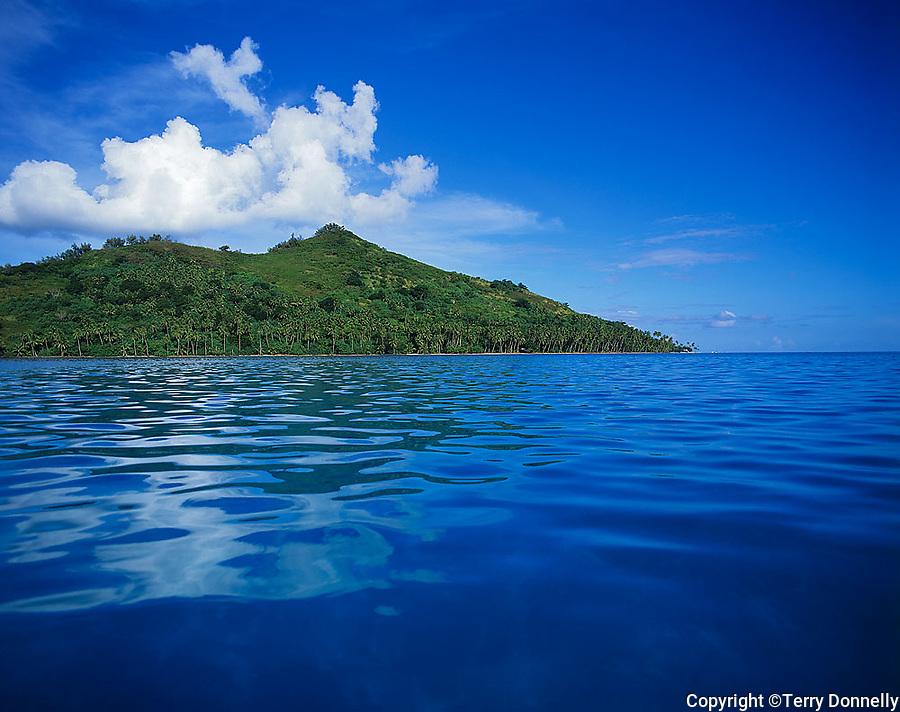 Bora Bora, French Polynesia   <br /> Motu Toopua with palm tree lined shore from the blue waters of Bora Bora lagoon