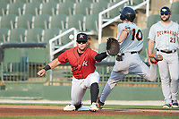 Corey Zangari (25) of the Kannapolis Intimidators stretches for a throw as Adam Hall (10) of the Delmarva Shorebirds lunges towards first base at Kannapolis Intimidators Stadium on June 4, 2019 in Kannapolis, North Carolina. The Intimidators defeated the Shorebirds 9-0. (Brian Westerholt/Four Seam Images)