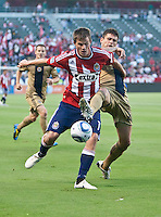 Chivas forward Justin Braun (17) prevents Philadelphia Union defender Cristian Arrieta (26) from getting to the ball during the first half of the game between Chivas USA and the Philadelphia Union at the Home Depot Center in Carson, CA, on July 3, 2010. Chivas USA 1, Philadelphia Union 1.