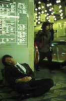 A salaryman passes out at the end of a long drinking session, eleven pm, Shinjuku station, Tokyo. There is a deep-rooted culture of after work drinking in Japan..