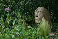 The garden is dotted with interesting sculptures such as this contemplative granite head framed by a bed of grasses and succulents