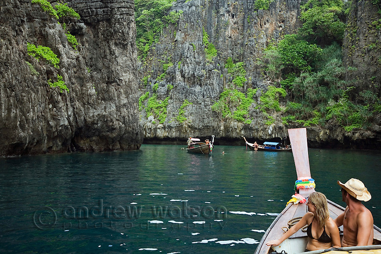 Tourists on a longtail boat cruise through the limestone cliffs of Ko Phi Phi Leh, Krabi province, THAILAND.