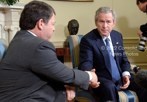 Washington, DC - February 8, 2006 -- United States President George W. Bush, right, meets with King Abdullah II of Jordan, left, in the Oval Office of The White House on February 8, 2006. In their remarks to the pool, both leaders condemned the cartoons that vilify the Prophet Mohammed and called for the end of the violence in response to the cartoon's publication. .Credit: Kevin Dietsch - Pool via CNP