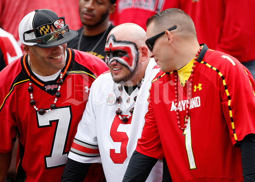 Ohio State fan Time Hurley, of Wapokoneta, Ohio watches the Buckeyes while sitting between his friends, and Maryland fans, Nate Rivers, left, of Lusby, Maryland and Chris Rushing of California, Maryland. during the third quarter of the NCAA football game at Byrd Stadium in College Park, Maryland on Oct. 4, 2014. (Adam Cairns / The Columbus Dispatch)