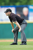 Umpire Cody Waterhouse handles the calls on the bases during the South Atlantic League game between the Charleston RiverDogs and the Hickory Crawdads at L.P. Frans Stadium on May 25, 2014 in Hickory, North Carolina.  The RiverDogs defeated the Crawdads 17-10.  (Brian Westerholt/Four Seam Images)