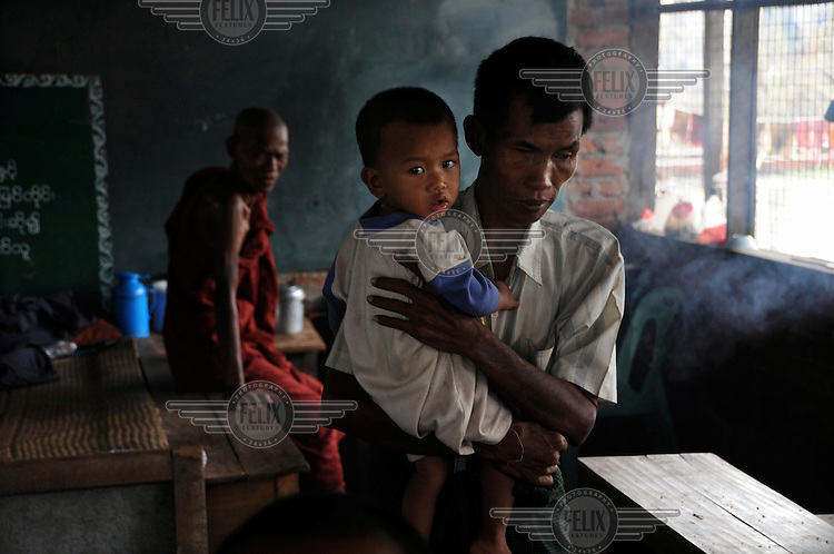 U Tin Hlaing, 45, a blind man, and his grandson Aung Phone Myint, 1. They are sheltering in the community school, which itself was badly damaged by Cyclone Nargis. Over 40 people drowned in this village alone, and virtually all the houses were destroyed. Cyclone Nargis hit Burma on 02/05/2008. Aye Yaw Gone village, Tha Mein Htaw township, Ayeyarawaddy Division.
