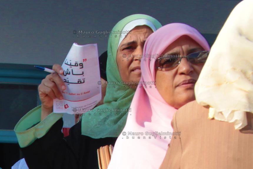 23 ottobre 2011 Tunisi, elezioni libere per l'Assemblea Costituente, le prime della Primavera araba: donne in coda davanti al seggio per votare. Una tiene in mano un volantino delle elezioni e una penna.<br /> Tunisie octobre <br /> tunisian elections