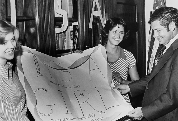 On his return to Washington after his baby's birth in Salt Lake City, Rep. David Daniel Marriott, R-Utah, was greeted by his personal secretary, Cristy Valetine (left) and assistant Julie Bakalian (center.) on July 18, 1977. (Photo by CQ Roll Call)