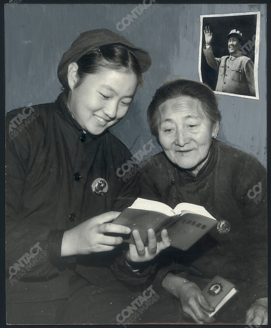 """During her """"reeducation,"""" a dancer from the Heilongjiang Province Song and Dance Company learns Mao Zedong's works with an elderly peasant woman; Xinsheng Commune, Qing'an County, Heilongjiang Province. November 4, 1969. The original picture was retouched prior to publication in order to show an unobstructed and sharply focused portrait of Mao on a clean-up background."""