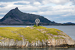 Monument marker to show crossing the Arctic Circle heading south on small island, Norway