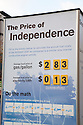 Close up of poster reading 'The Price of Independence' compares the costs of driving a gas car versus an electric vehicle. Nissan Leaf Zero Emission Tour promotional event for the Nissan Leaf electric car that is scheduled to be released in Fall 2010. Car specs from Nissan: 5 person capacity, 90 MPH top speed, lithium-ion battery, 100 mile average range per charge. Santana Row, San Jose, California, USA, 12/5/09