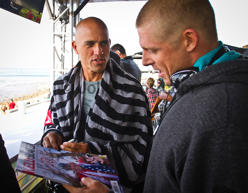 "LOWER TRESTLES, California/USA (Wednesday, September 21, 2011) Mick Fanning (AUS) gets an autograph from Kelly Slater (USA).  - Kelly Slater (USA), 39, has won his fifth Hurley Pro at Trestles title, defeating Owen Wright (AUS), 21, in a hard-fought Final that saw the iconic Floridian overtake the young Australian in a last-minute exchange with a final score of 17.50 to 16.74...Slater and Wright's third consecutive Final bout marks a first in ASP history, as no two competitors have faced off in three successive ASP Dream Tour Finals - a noteworthy statistic in sparking this new rivalry in the battle for the ASP World Title...Slater roared to life on the Final day, unloading the highest heat-total of competition, 18.40 out of 20 in the Semifinals, and maintained his lethal form throughout the day's entirety with a consistent display of new-school airs and patented carves to clinch his unprecedented 48th elite ASP World Tour victory and third of the season...""Owen (Wright) is tough and he's been surfing great,"" Slater said. ""There really are no weak points to his surfing and he's going to be a standout in every spot. A lot of the guys tried to get him this week and I got lucky in that last exchange. I was taking the first wave of the set under his priority and once I got priority I wanted to wait. It almost looked like there wasn't a wave after Owen's. It's been fun surfing against Owen and surfing Lowers. It's been a great week and thanks everyone for the crazy support, it's been wonderful.""..Wright, current No. 2 on the ASP World Title rankings, has continued to build momentum throughout his sophomore year amongst the ASP Top 34 and dispatched of a rampaging Mick Fanning (AUS), 30, and rookie prodigy Julian Wilson (AUS), 22, en route to his rematch against Slater, but was unable to solidify the victory over the veteran in the Final.  Photo: joliphotos.com"