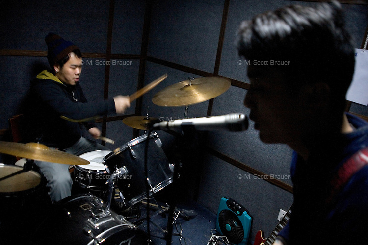 Punk rock musicians Jobby (left) and Gao Feng practice late at night in the back room of Gao Feng's tattoo parlor in Nanjing, China.