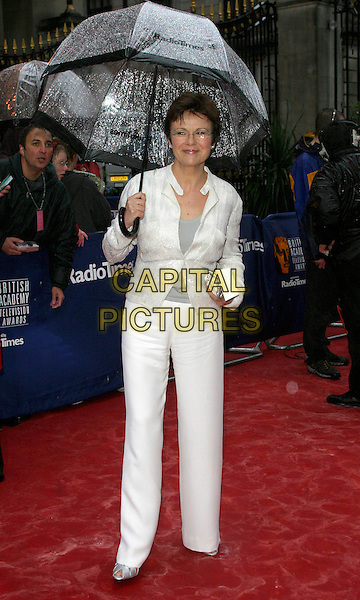 JULIE WALTERS.BAFTA TV Awrds, Grosvenor House Hotel, London, .18th April 2004..full length raining wet red carpet white trousers suit umbrella glasses.Ref: BR.www.capitalpictures.com.sales@capitalpictures.com.©Capital Pictures.