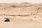 A jeep drives past frankincense trees and through the rocky desert in Oman.