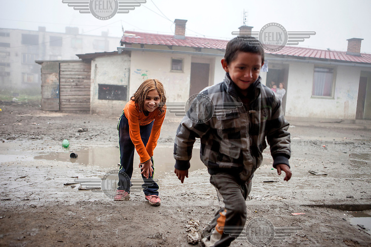 A boy and a girl playing a game with coins on a muddy patch of ground in the middle of the Roma settlement located in 'Budulovskej Street'.