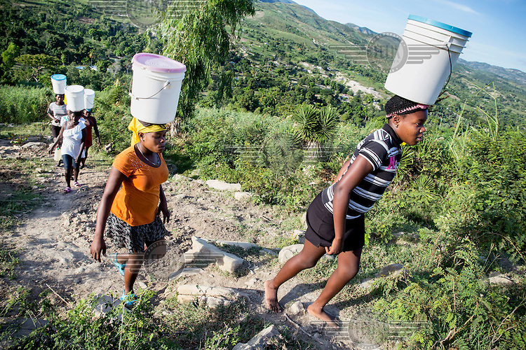 Lousnaica Nore, 17 years old, (orange t-shirt) and sister Angeline Nore, 15 years old (black and white t-shirt) live near the source of the river Moustique in Haut-Moustique. They are responsable for their family's water supply and together carry some 75 litres of water per day. They used to fetch this water from the river but since Belgian NGO PROTOS constructed water stand pipes in their village they can now fetch the water from it. They still have to carry the water up a hill but prefer this to the longer journey to the river and furthermore the river water wasn't clean and caused the family bouts of diarrhoea. They fetch the water before and after going to school.