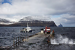 People wait to board the ferry on the pier outside of the village of Svínoy in the Faroe Islands.