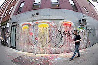 A wall decorated with graffiti style street art in the trendy Bowery neighborhood of New York on Saturday, May 26, 2012. (© Frances M. Roberts)