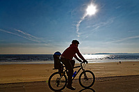 Pictured: A man cycles with his young child at Swansea seafront in Wales, UK. Friday 23 February 2018<br /> Re: Parts of the UK have been enjoying sunshine with freezing cold temperatures.