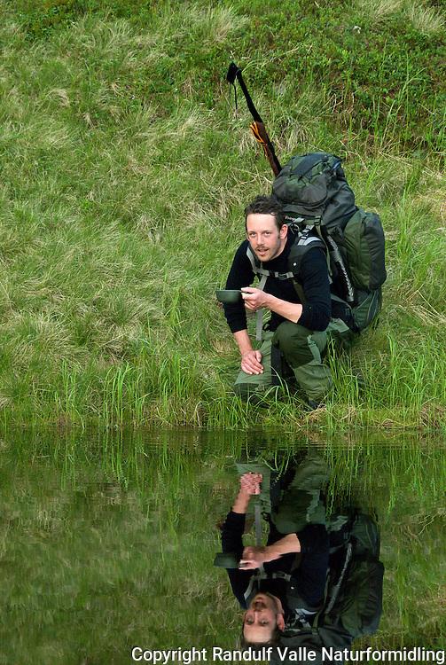 Mann med ryggsekk drikker vann. ---- Man with back pack drinking water.