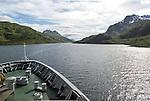 Hurtigruten ferry ship passing down fjord Raftsundet, Hinnoya Island, Nordland, northern Norway