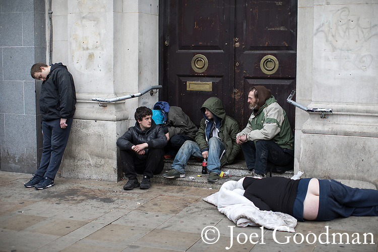 © Joel Goodman - 07973 332324 . 06/04/2017 . Manchester , UK . A group of men huddle in a doorway on Piccadilly Gardens , one lies in an unresponsive state on the pavement , another stands slouched back against the wall . An epidemic of abuse of the drug spice by some of Manchester's homeless population , in plain sight , is causing users to experience psychosis and a zombie-like state and is daily being witnessed in the Piccadilly Gardens area of Manchester , drawing large resource from paramedic services in the city centre . Photo credit : Joel Goodman