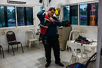 Journalist Jesus Olivares dresses himself in the Bomberos, firefighters uniform, at a Fire Station, where he volunteers on June 29, 2016 in Veracruz, Mexico. <br /> Photo Daniel Berehulak for the New York Times