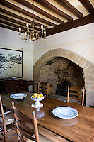 The traditional dining room is dominated by the restored arched stone fireplace