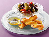bowl of mixed olives with bread sticks