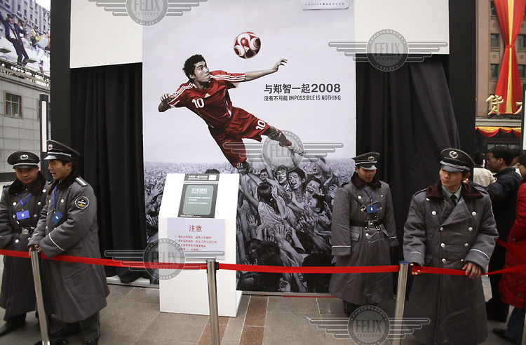 2008 Olympic Games poster, featuring a Chinese football player, stands behind guards protecting one of the stands during an Adidas promotional event...