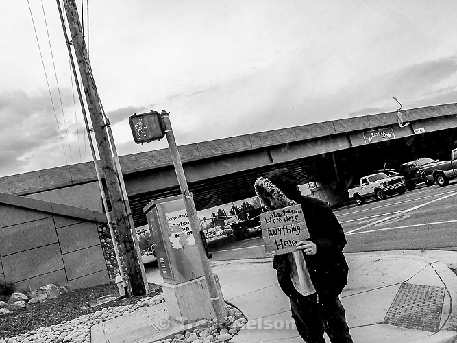 guy on freeway off ramp with sign: homeless, anything helps, Monday April 1, 2013.