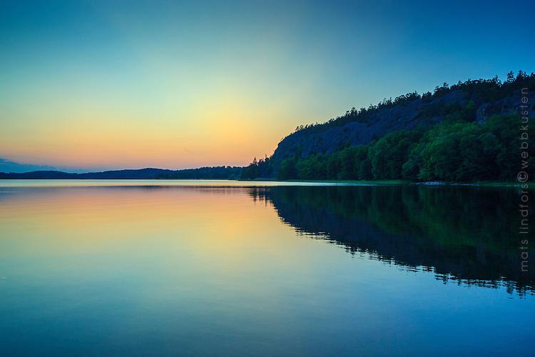 Kalvfjärden ligger spegelblank vid solnedgången i Tyresö-Brevik Stockholms skärgård. / Sunset in Stockholm archipelago Sweden.