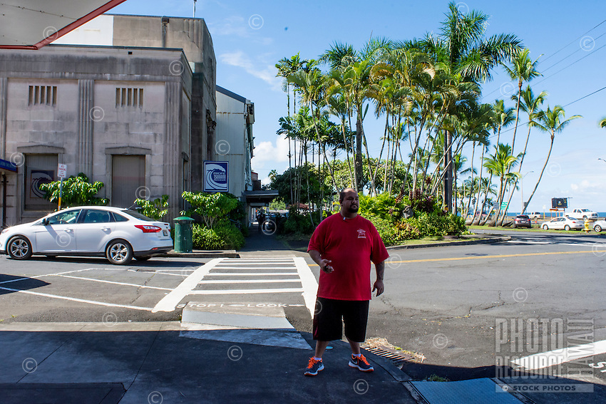 A local resident stands on a street corner near the waterfront with the Pacific Tsunami Museum behind him, downtown Hilo, Big Island of Hawai'i.