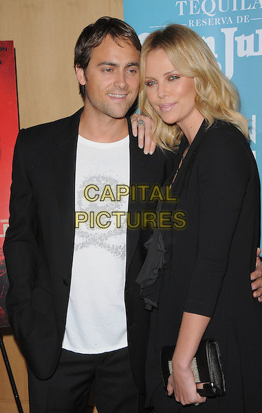 "STUART TOWNSEND & CHARLIZE THERON .The Redwood Palms Pictures & Genart Screening of ""Battle in Seatte"" held at The Clarity Theater in Beverly Hills, California, USA. .September 22nd, 2008                                                                     half length dress black lace up laces clutch bag ruffle suit couple white top .CAP/DVS.©Debbie VanStory/Capital Pictures."