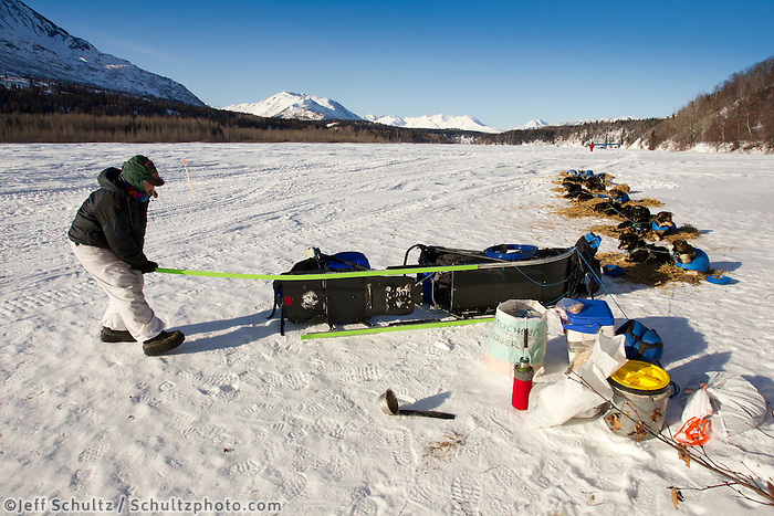 Judy Currier changes sled runners during a break on the Skwenta River between Finger lake and Rainy Pass during Iditarod 2011