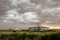 Tractor & abandoned house beneath stormy sky in Levelland, TX