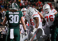 Ohio State players celebrate a touchdown by running back Ezekiel Elliott (15) behind Michigan State Spartans linebacker Riley Bullough (30) during the fourth quarter of the NCAA football game at Spartan Stadium in East Lansing, Michigan on Nov. 8, 2014. (Adam Cairns / The Columbus Dispatch)