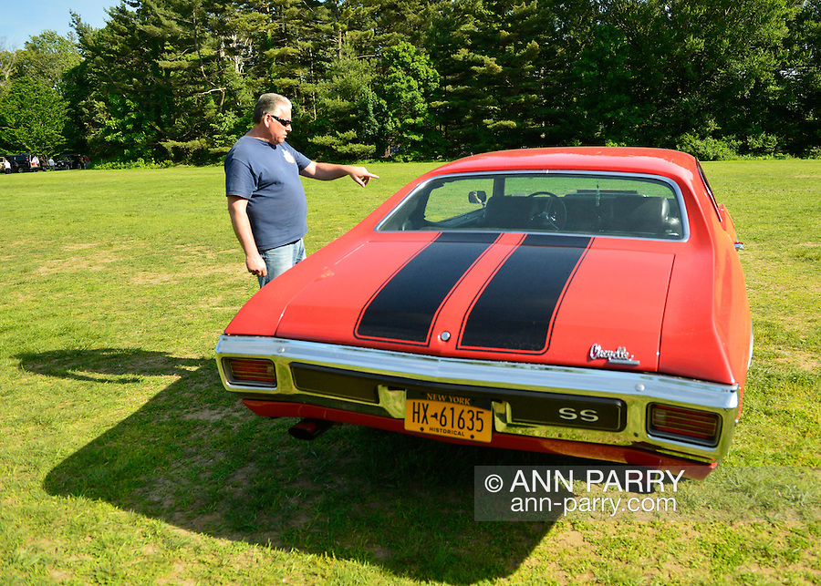 Old Westbury, New York, U.S. - June 1, 2014 -  Owner JOHN McALEESE of SEAFORD points to his iconic red with black stripes muscle car 1970 Chevrolet Chevelle SS 396 - 350 base model. McAleese visited the Antique and Collectible Auto Show held on the historic grounds of elegant Old Westbury Gardens in Long Island, and sponsored by Greater New York Region AACA Antique Automobile Club of America.