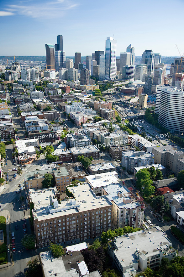 A sunny, summer afternoon aerial photo of Seattle, Washington's Belltown / Denny Triangle neighborhood showing skyscrapers of the downtown Seattle skyline behind and the orange construction cranes that signified the building boom of the early 21st century.
