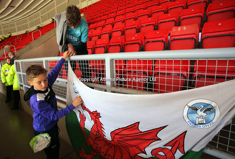 Swansea supporters tie a welsh flag onto the railings prior to the Premier League match between Sunderland and Swansea City at the Stadium of Light, Sunderland, England, UK. Saturday 13 May 2017