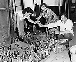 After the flood, liquor had to be inspected for possible pollution. Here at the spot on Riverside Street where the Rendezvous Restaurant operated, liquor bottles are being sorted. From left, Theresa Pocus, Stella Seksneus, cook for the Rendezvous Restaurant, and William Dapsis, owner of the establishment.