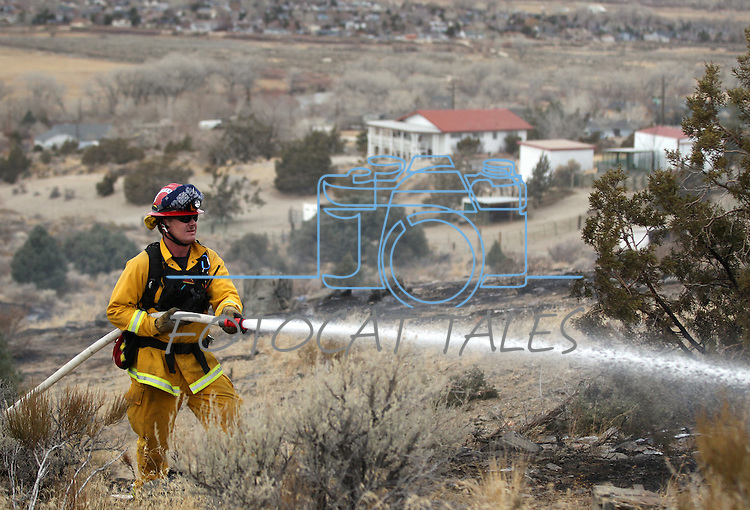 A Carson City fire captain puts out hot spots on a 150-200 acre brush fire east of Carson City, Nev., on Friday, Dec. 30, 2011. Initially the fire threatened about two dozen homes before being pushed east by high winds. (AP Photo/Cathleen Allison)