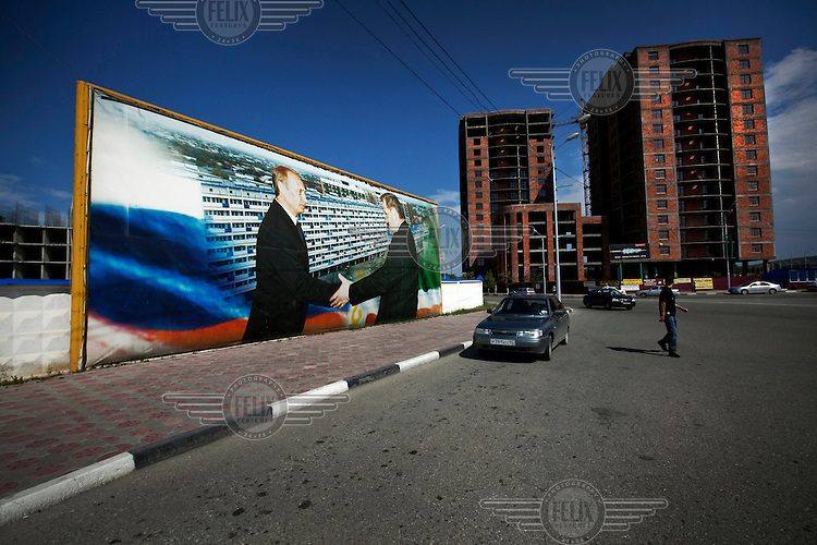 A poster of Russian prime minister Vladimir Putin shaking hands with former Chechen president Akhmad Kadyrov, next to newly constructed buildings. After the war, no buildings were left standing, but the city is now undergoing rapid regeneration.