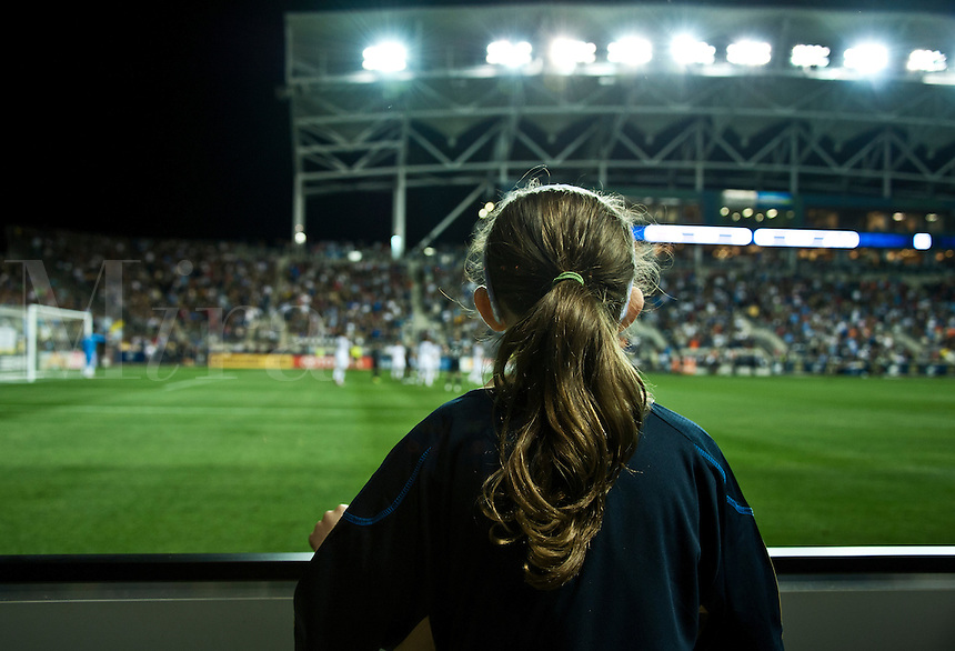 Young fan watches pro soccer match.
