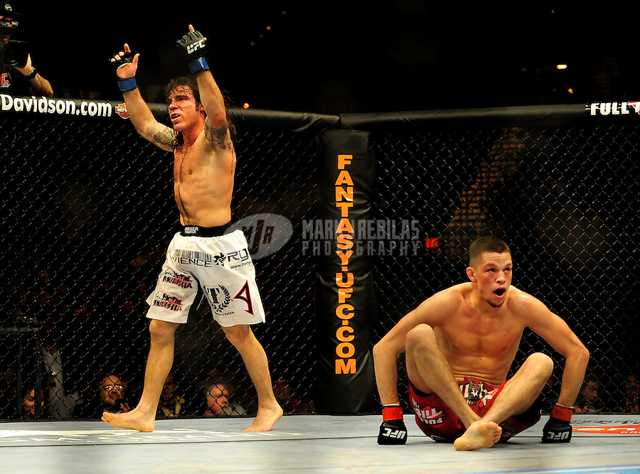 Jan. 31, 2009; Las Vegas, NV, USA; UFC fighter Clay Guida (white trunks) raises his arms after knocking down Nate Diaz (red trunks) during the lightweight bout in UFC 94 at the MGM Grand Hotel and Casino. Guida defeated Diaz on a split decision. Mandatory Credit: Mark J. Rebilas-