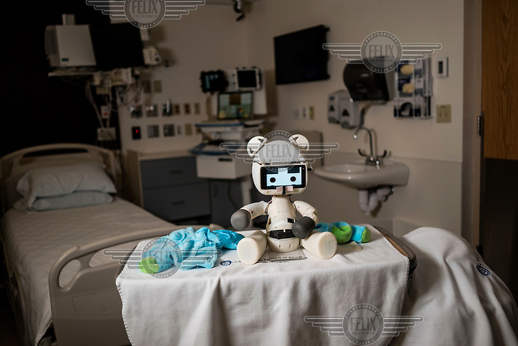 The Huggable Bear, a social robotic stereotype, sits on a table at Boston's Children Hospital next to it's remote control station. Huggable is being used in an experiment between Boston's Children Hospital and the Massachusetts Institute of Technology (MIT). The goal of the experiment is to determine whether a so called 'Huggable' teddy bear, a social robotic stereotype, can have therapeutic value for children who have to endure long hospital stays. The bear's talking and movements are remotely controlled by Hospital Staff from outside of the room.
