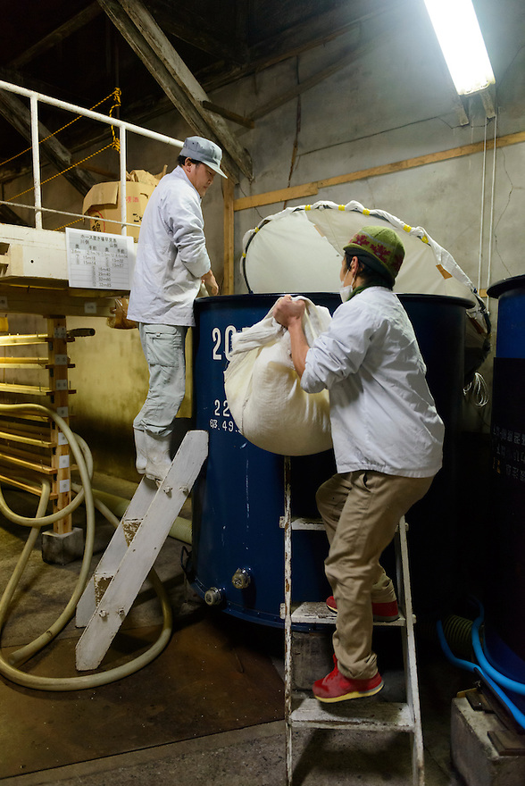 "Brewery workers adding rice to fermenting sake. Tsuji Honten Sake, Katsuyama town, Okayama Prefecture, Japan, February 1, 2014. Tsuji Honten was founded in 1804 and has been at the cultural centre of the town of Katsuyama for over two centuries. 34-year-old Tsuji Soichiro is the 7th generation brewery owner. His elder sister, Tsuji Maiko, is the ""toji"" master brewer."