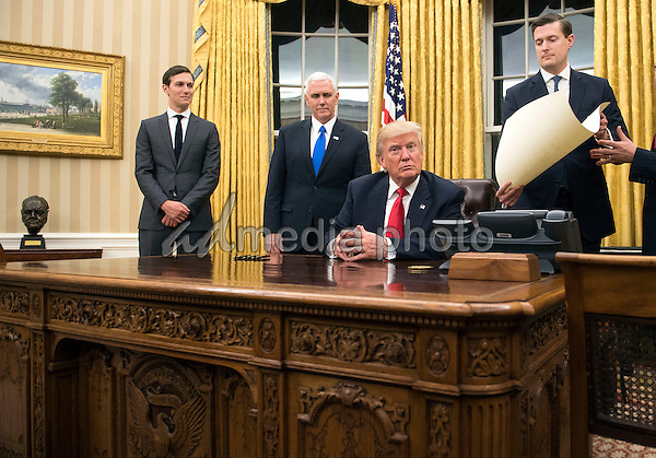 President Donald Trump prepares to sign a confirmation for Defense Secretary James Mattis in the Oval Office at the White House in Washington, D.C. on January 20, 2017. Photo Credit: Kevin Dietsch/CNP/AdMedia